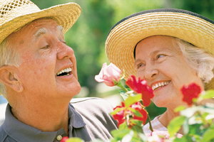 Close-up of seniors, man and woman in straw hats looking at flowers outdoors.